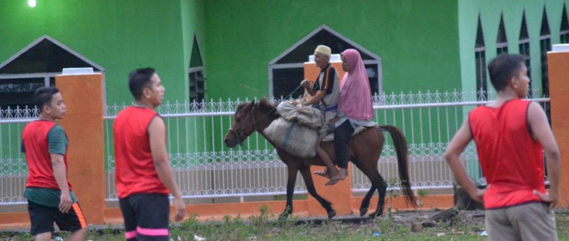 H Cale dan Hj Tombong melintas dwngan kudanya.